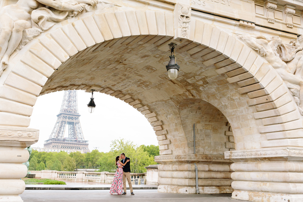 couple portrait under the arch of bir-hakeim bridge with view of eiffel tower at sunrise captured by paris photographer federico guendel