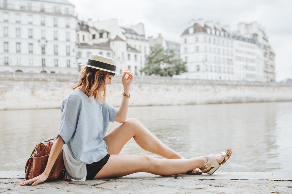 paris photographer fashion blogger lifestyle portrait with straw hat by the seine river in summer