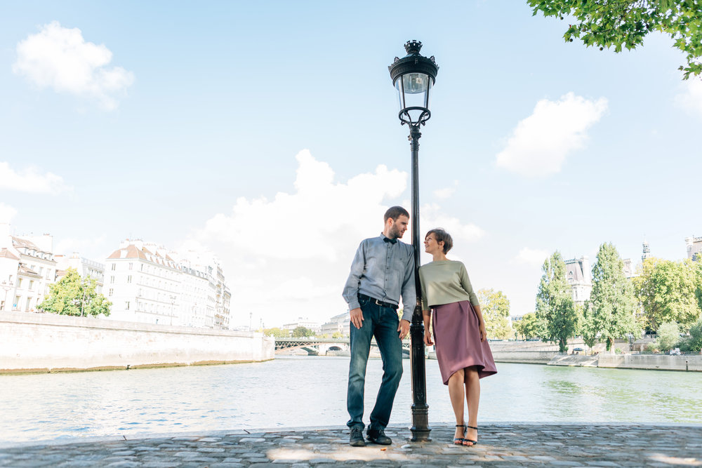 paris photographer honeymoon couple portrait by lamp post at ile saint louis by the seine river