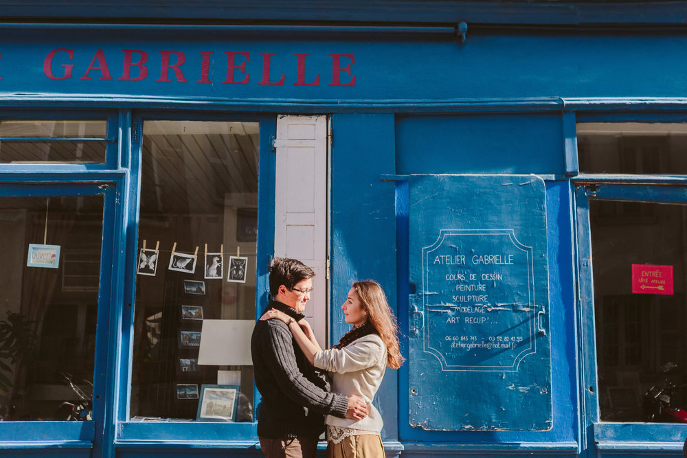 paris photographer engagement couple portrait by blue wall in montmartre