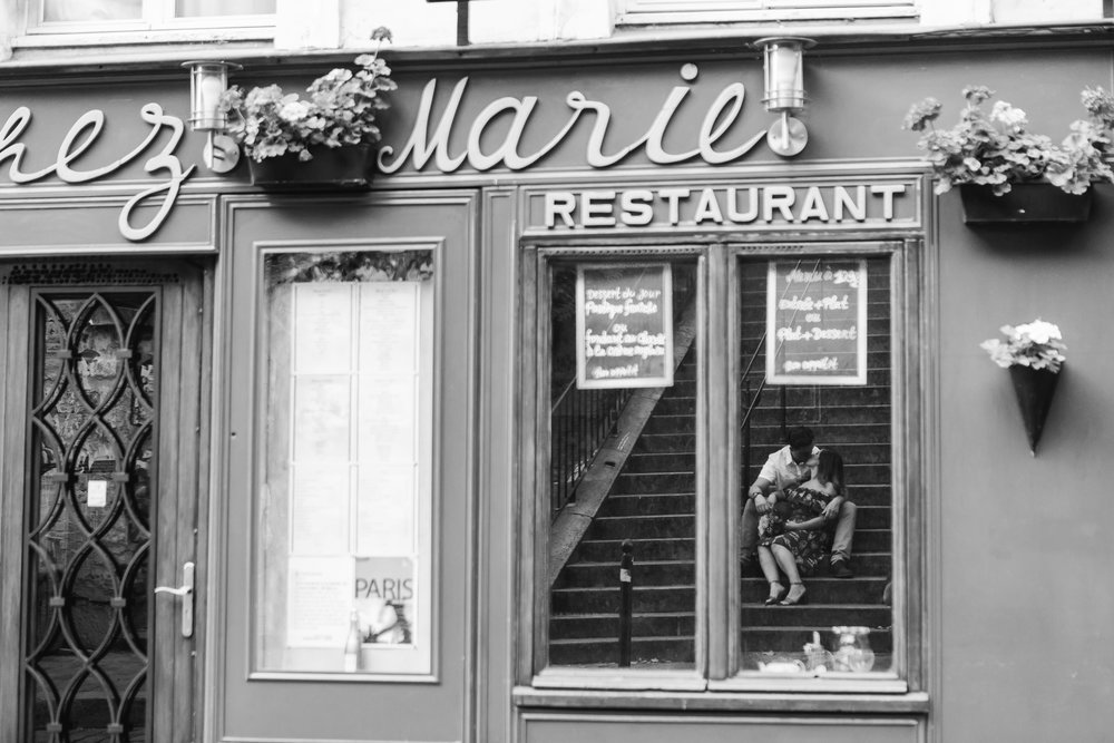 paris photographer couple portrait in black and white window reflection by chez marie restaurant in montmartre