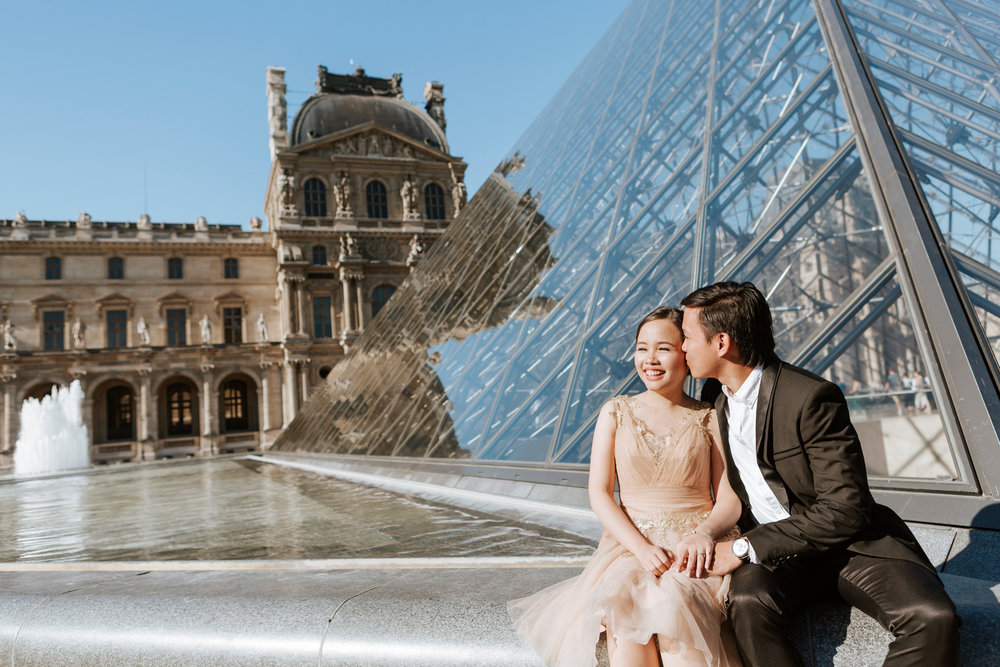 Pre-wedding couple portrait kissing at the courtyard of the Louvre Museum by the Pyramid captured by Paris Photographer Federico Guendel