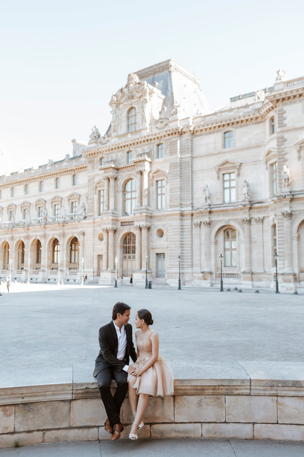 Pre-wedding couple portrait sitting in the courtyard of the Louvre Museum captured by Paris Photographer Federico Guendel