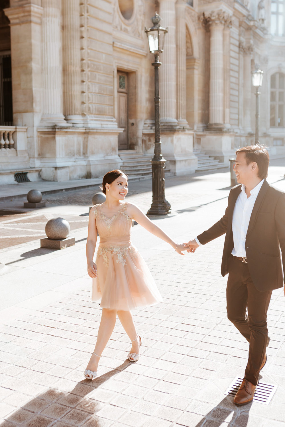 Pre-wedding couple portrait walking the courtyard of the Louvre Museum captured by Paris Photographer Federico Guendel