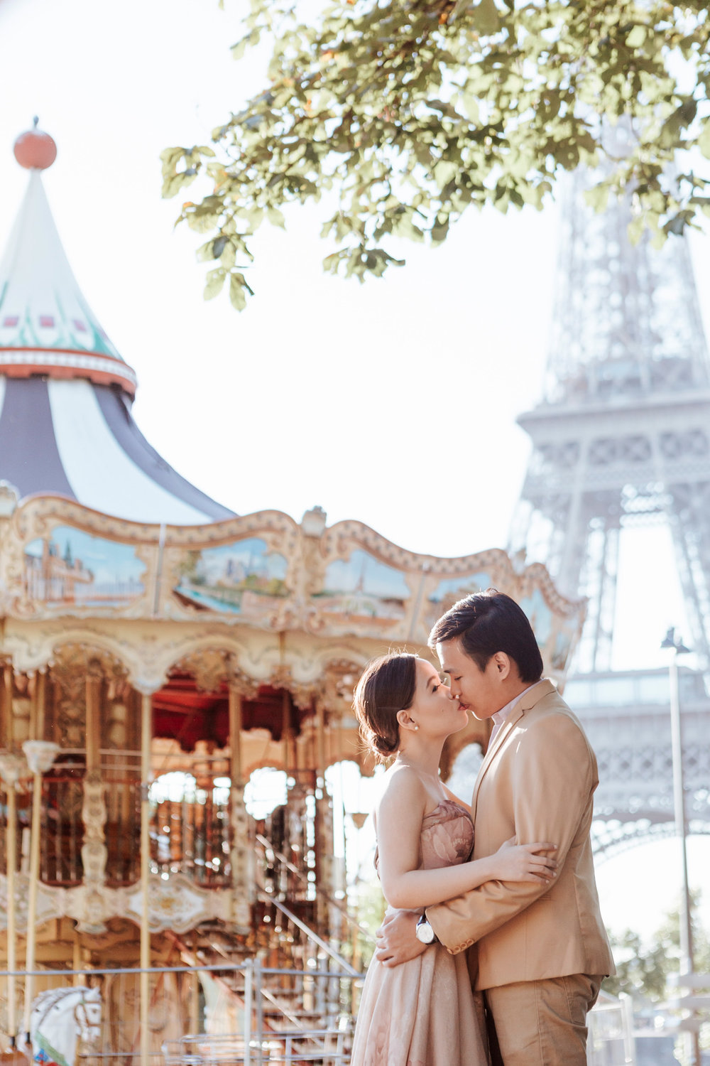 Pre-wedding couple portrait session kissing by the carousel at the Eiffel Tower in sunrise captured by Photographer in Paris Federico Guendel