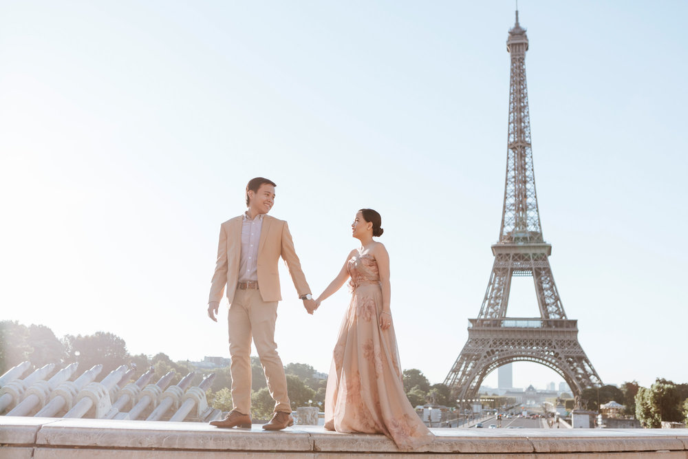 Pre-wedding couple portrait session holding hands walking by the Eiffel Tower at Trocadero in sunrise captured by Photographer in Paris Federico Guendel