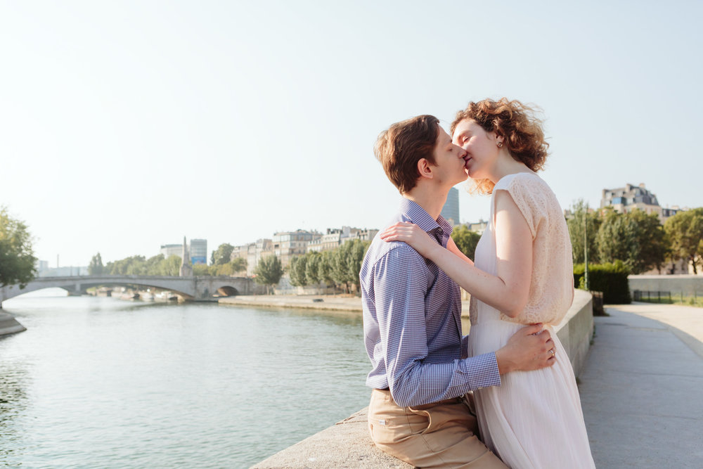 Couple in love kissing by rive Seine at Ile de la Cite in Paris captured by Paris Photographer Federico Guendel IheartParisFr