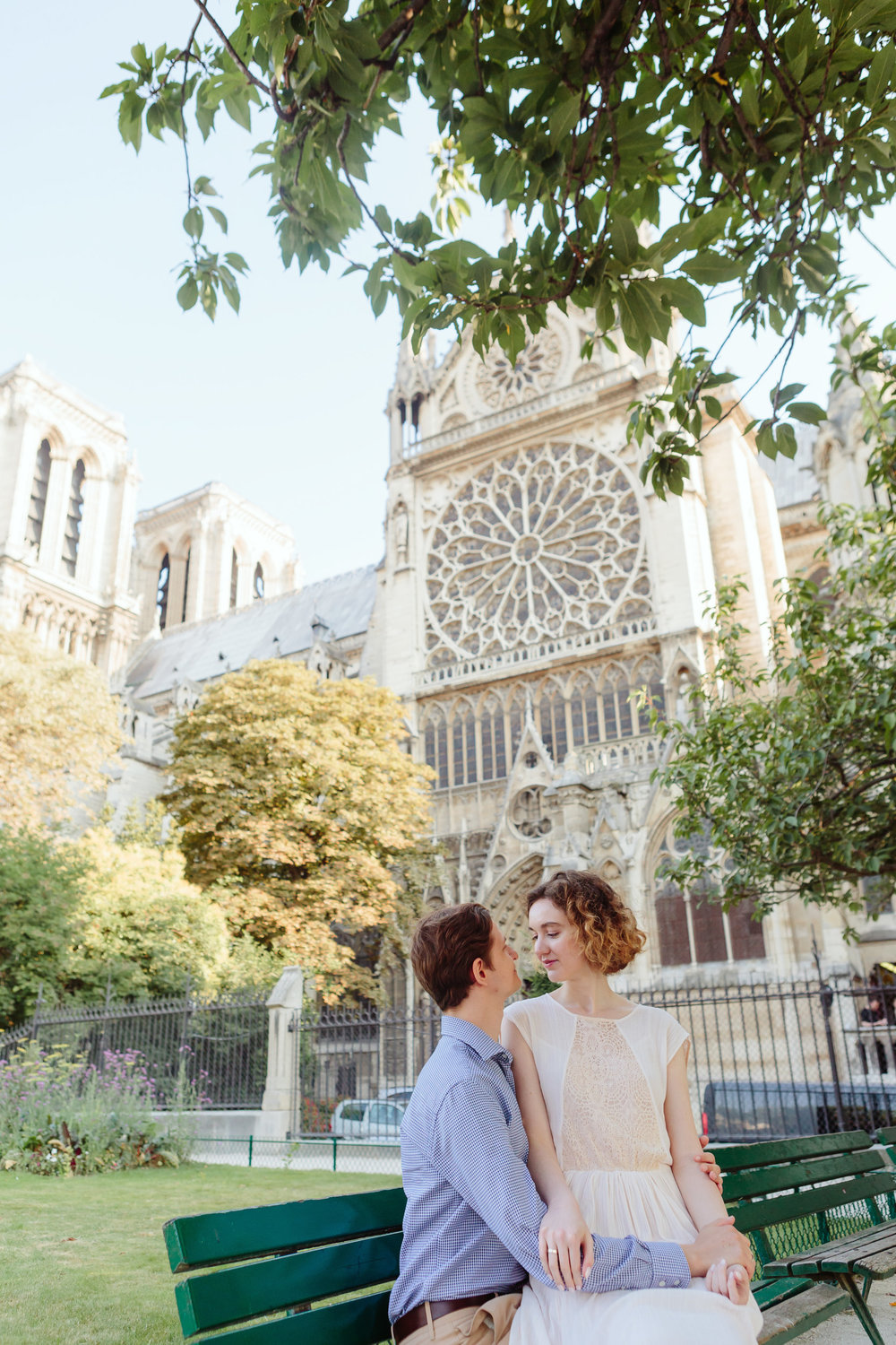 Couple in love sitting on a bench by Notre Dame Cathedral in Paris captured by Paris Photographer Federico Guendel IheartParisFr