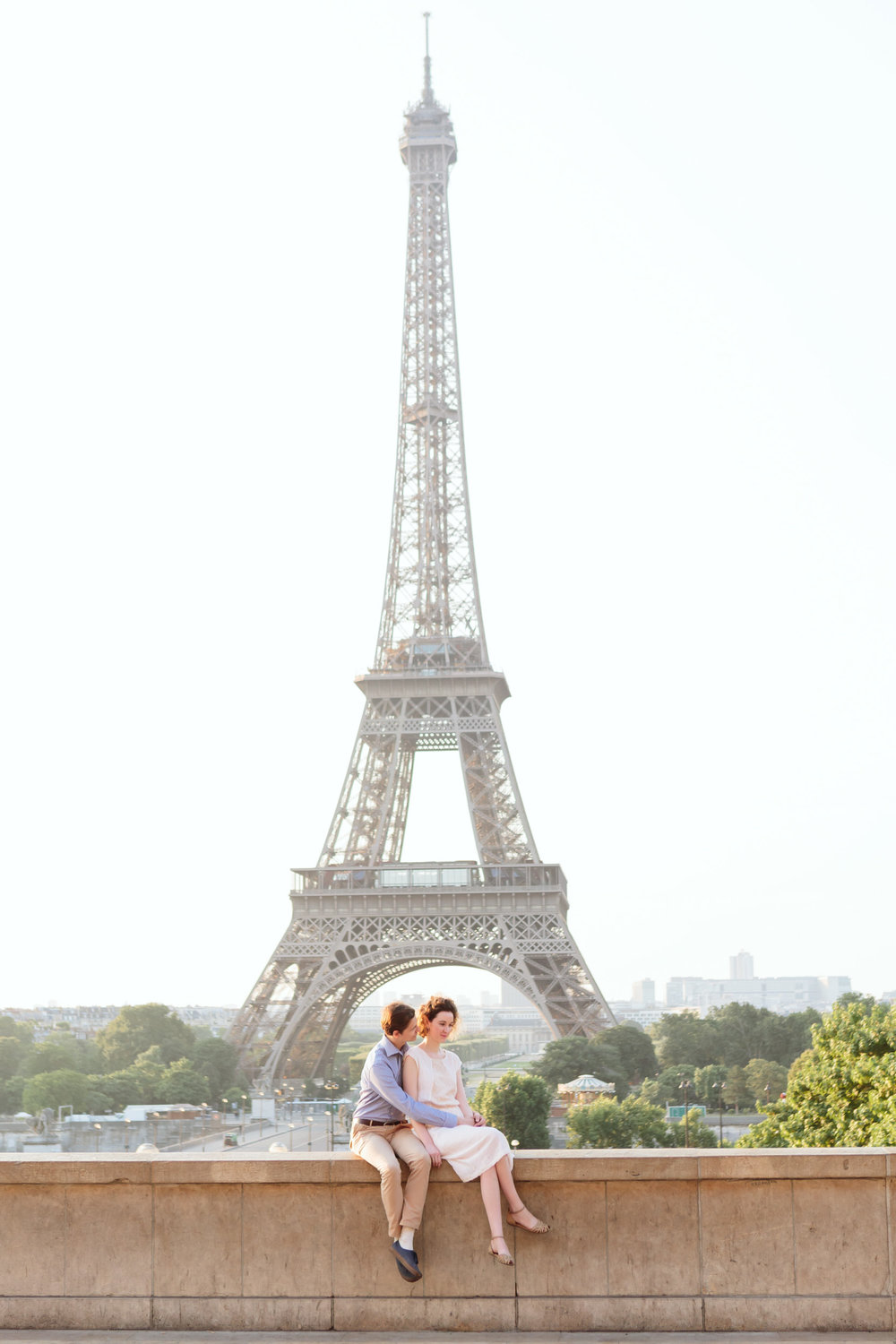Couple in love sitting at Trocadero by the Eiffel Tower at sunrise captured by Paris Photographer Federico Guendel IheartParisFr