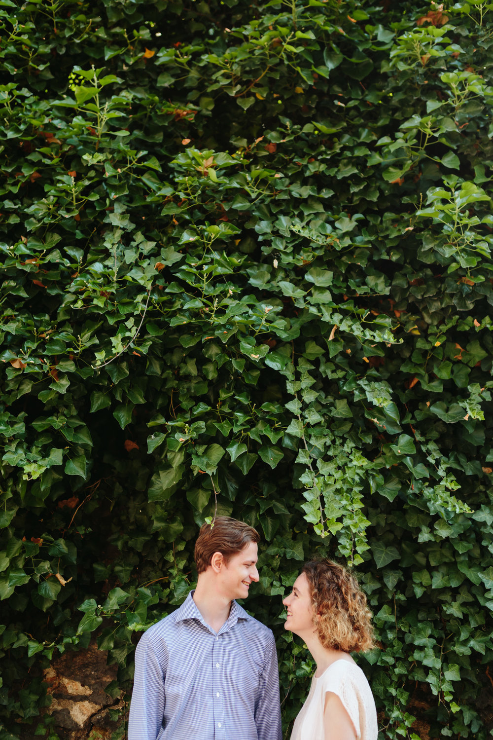 Couple in love smiling standing by wild ivy wall at Montmartre captured by Paris Photographer Federico Guendel IheartParisFr