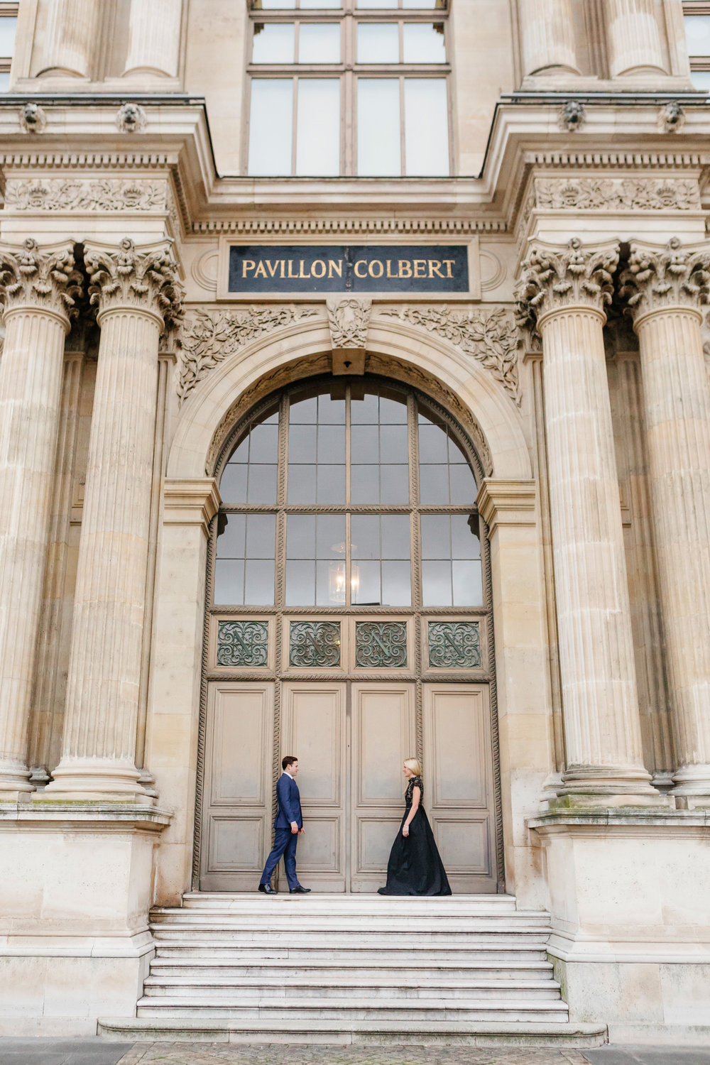 Paris vacation couple portrait standing by the door of Pavillon Colbert at Louvre Museum captured by Paris Photographer Federico Guendel www.iheartparis.fr