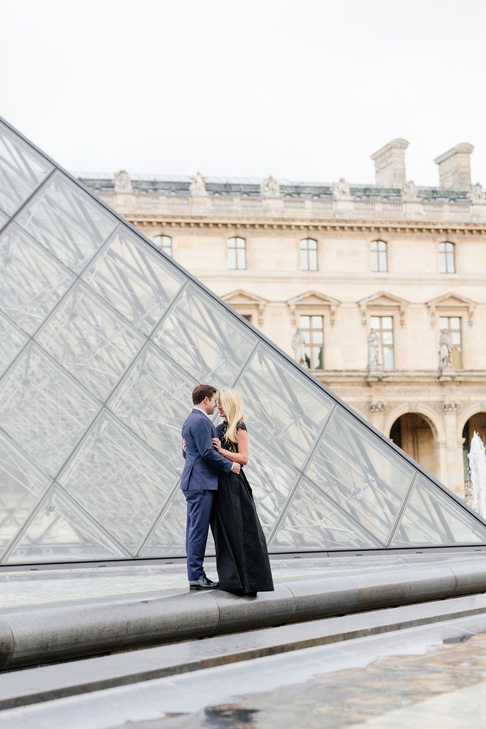 Paris vacation couple portrait standing by the Louvre Museum Pyramid captured by Paris Photographer Federico Guendel www.iheartparis.fr