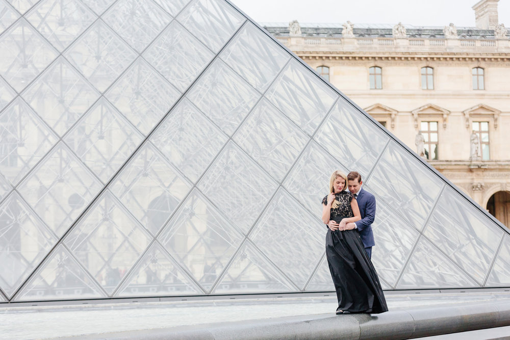 Paris vacation couple portrait standing in the courtyard of Louvre Museum by the Pyramid captured by Paris Photographer Federico Guendel www.iheartparis.fr