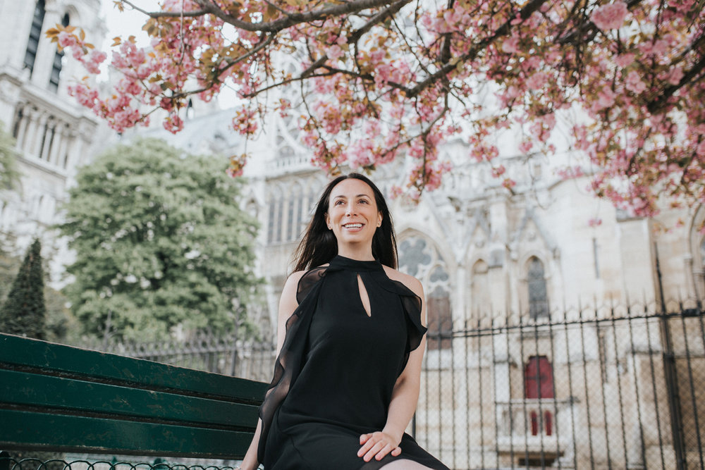 Spring portrait of Rebecca Plotnick founder of Every Day Parisian blog in front of Notre Dame and cherry blossoms captured by Paris Photographer Federico and Anastasia Guendel IheartParisFr TheFlyingPoodle