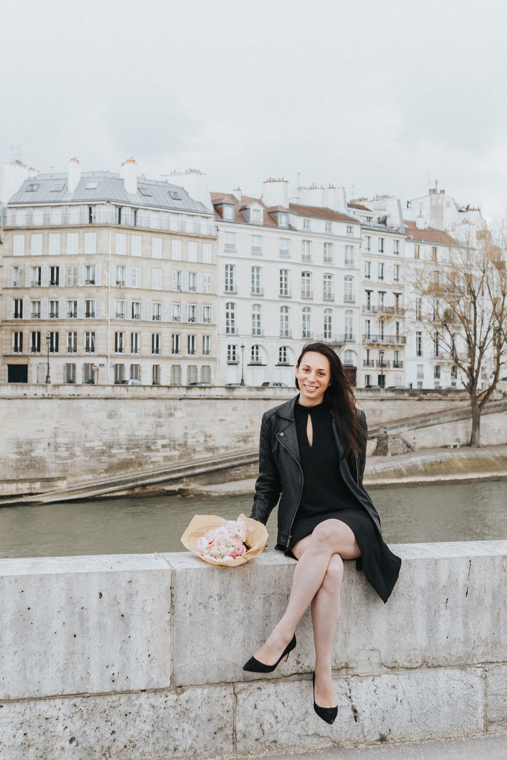 Spring portrait of Rebecca Plotnick founder of Every Day Parisian blog sitting by the Seine river and Ile Saint Louis with bouquet of ranunculus captured by Paris Photographer Federico and Anastasia Guendel IheartParisFr TheFlyingPoodle