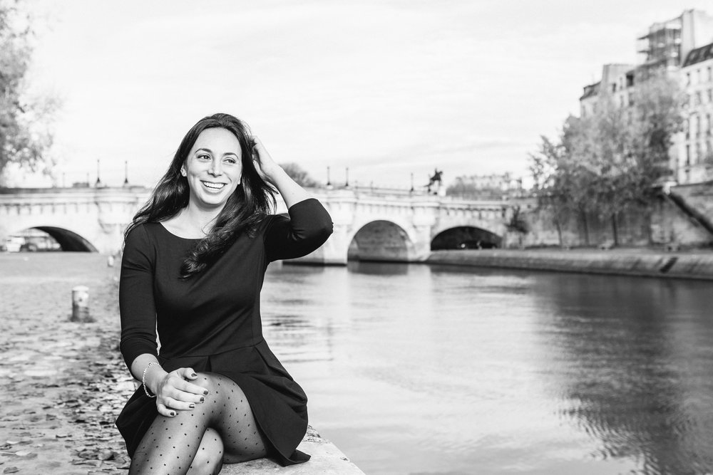 Black and white portrait of Rebecca Plotnick founder of Every Day Parisian blog sitting by the Seine river captured by Paris Photographer Federico and Anastasia Guendel IheartParisFr TheFlyingPoodle