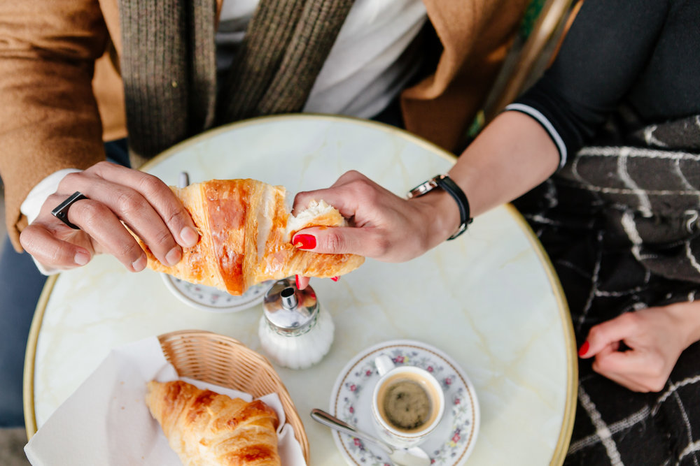 Couple sharing croissant at cafe Esmeralda captured by Paris Photographer Federico Guendel IheartParis www.iheartparis.fr