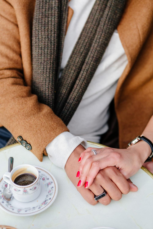 Close up of a couple holding hands at cafe Esmeralda captured by Paris Photographer Federico Guendel IheartParis www.iheartparis.fr