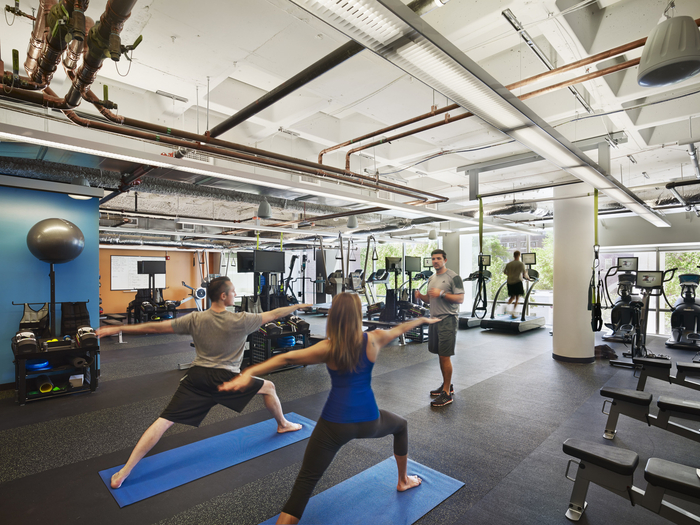 Employees at Google's Cambridge Office in Boston take a yoga break in the company's fitness center. Photo from Office Snapshots.