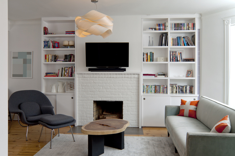 Custom cabinetry, radiator riser enclosure and simple fireplace surround conceal TV wiring and provide open and closed storage.