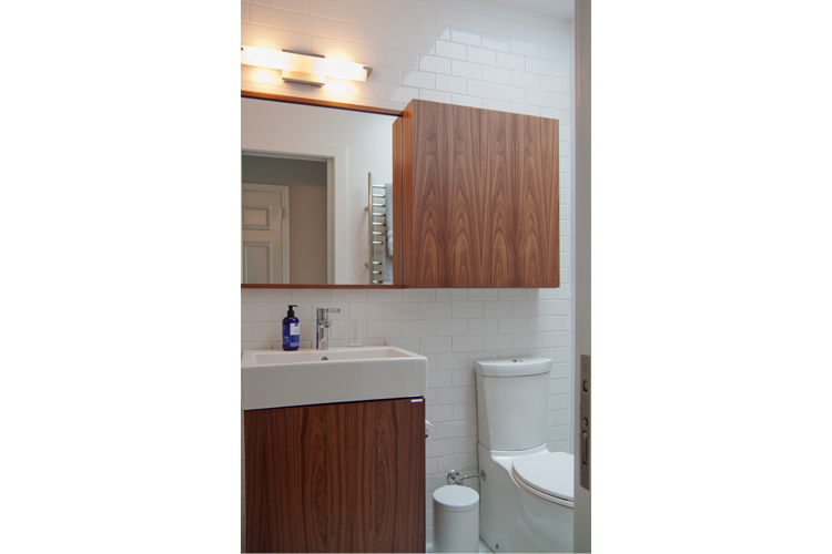 A unified storage solution with a mirror/cabinet/shelf and matching vanity built for a pocket-sized bathroom.