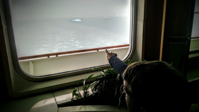 Tom spotting tiny icebergs from the lounge where we played trivia