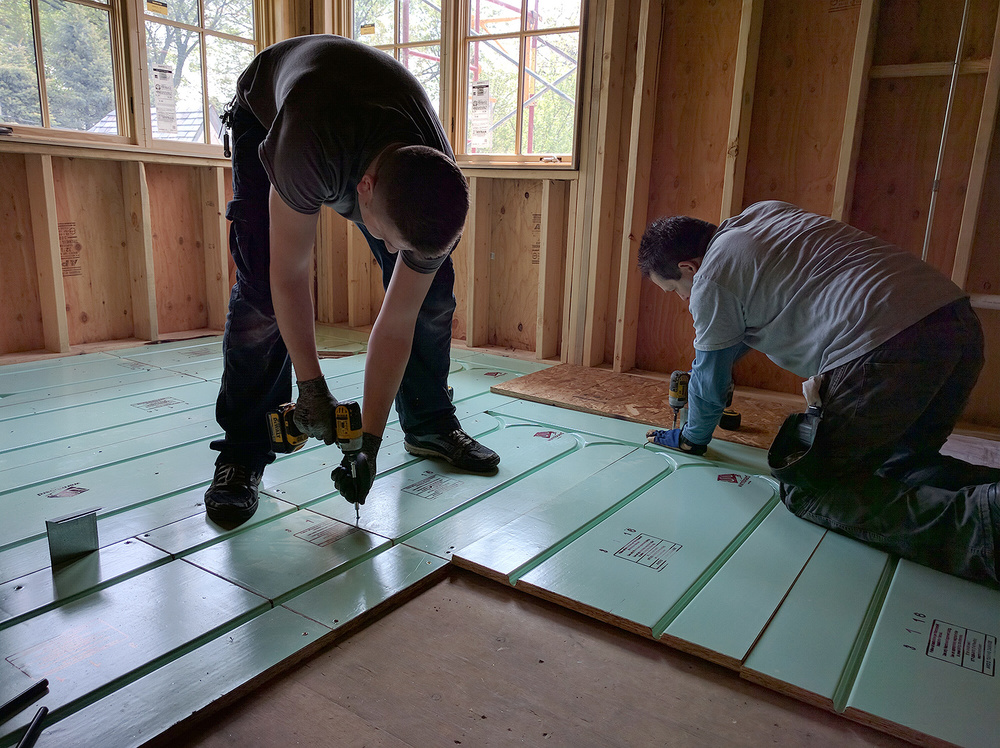 Warmboard panels are cut, aligned and installed over the subfloor.