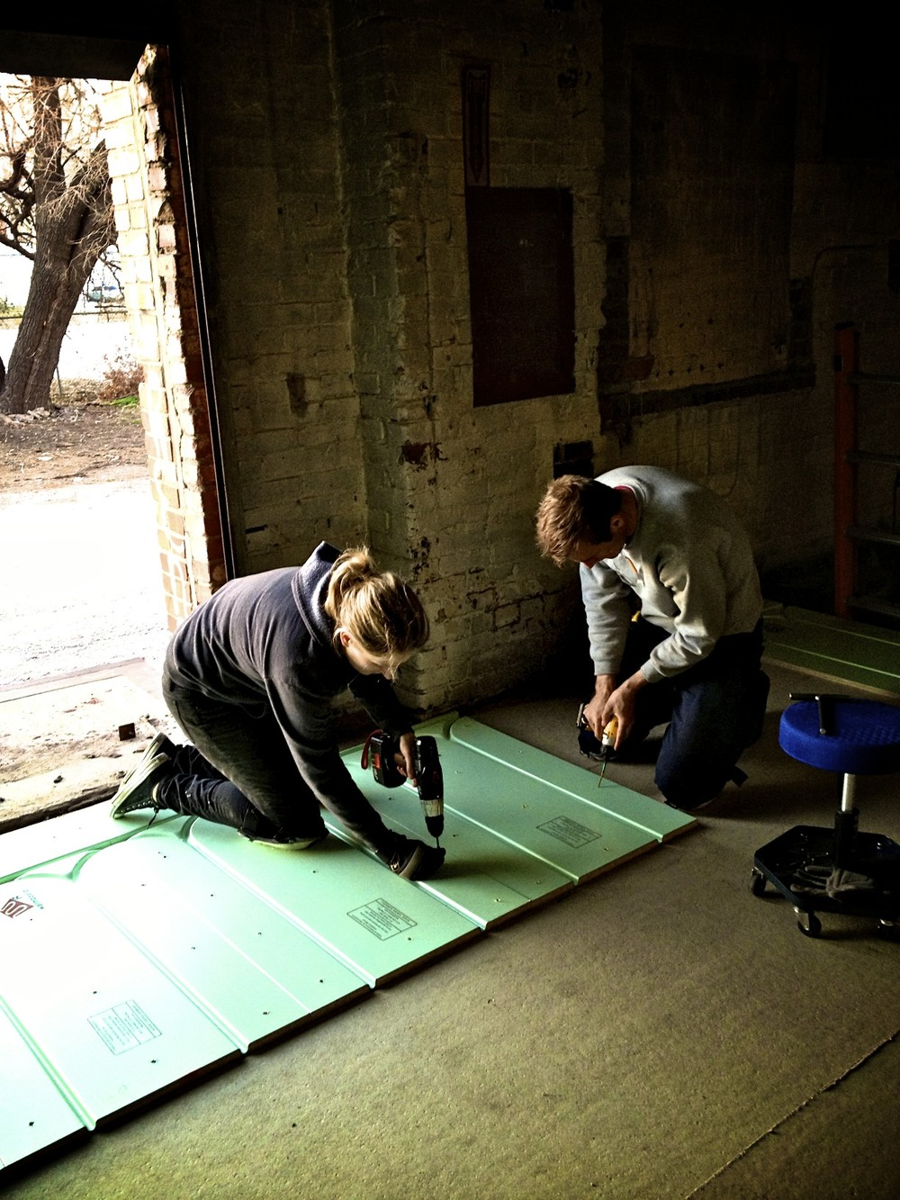 Callie and Jeremy install the first few Warmboard-R panels into their new home.