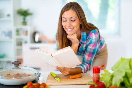 100178913-beautiful-young-woman-cooking-healthy-meal-in-the-domestic-kitchen-she-is-reading-recipes-from-the-c.jpg