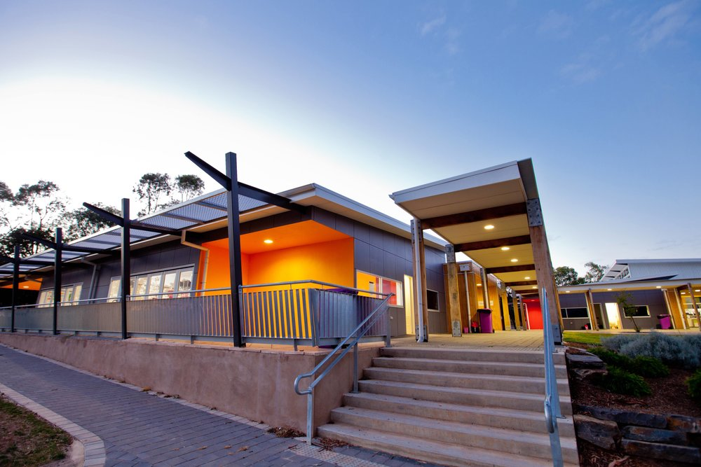 Willunga High School | Middle School Development   Two linked buildings, each containing six classrooms accessed from a central circulation studio. Each classroom contains a breakout space as well as direct access to outdoor landscaped areas via cafe style doors.
