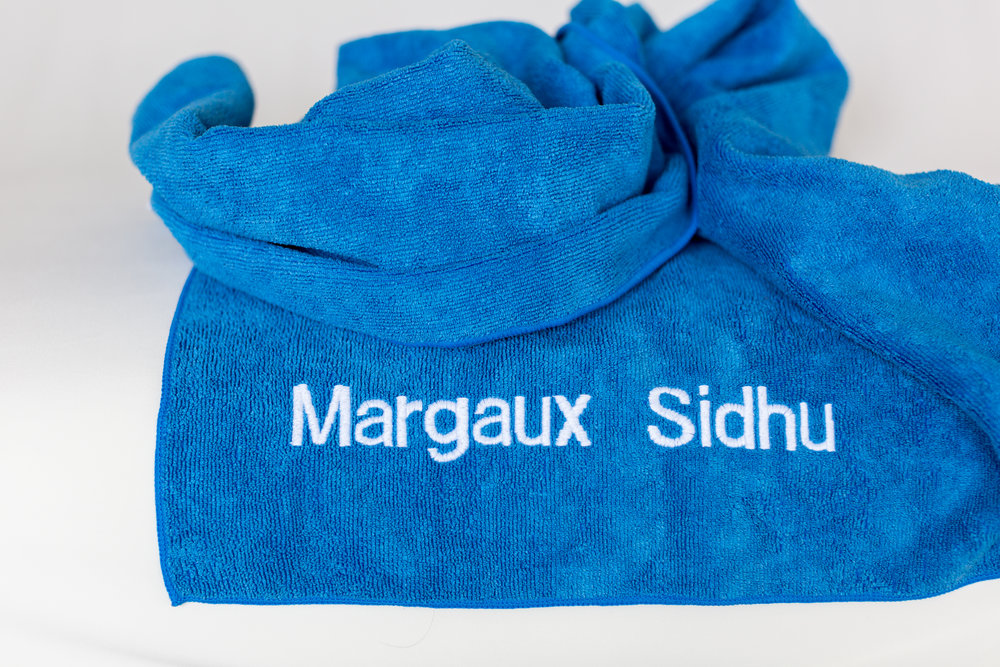 2. The women artisans expertly embroider the towel (text or logo). -