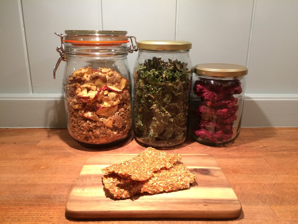 Carrot pulp crackers hanging out with other dehydrated goodies: raw apple granola, kale crisps and berry  bars