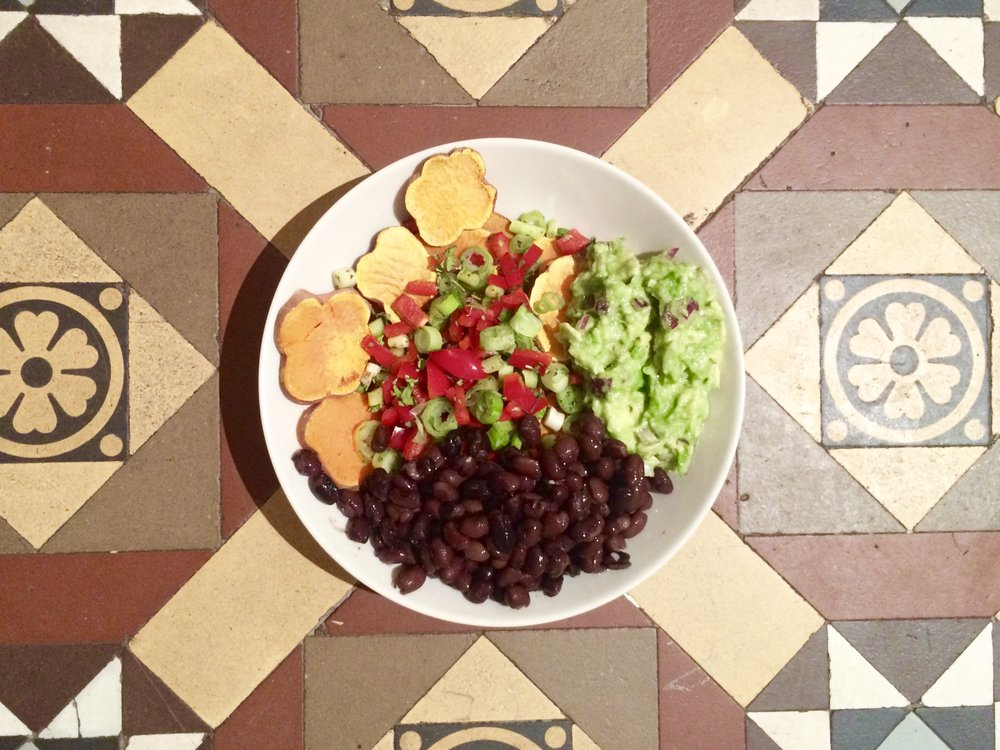 Taco salad with roasted sweet potatoes, black beans, red pepper, spring onions and guacamole