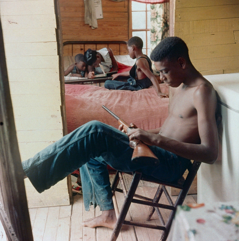 """blackhistoryalbum :      The Way It Was……Mobile, Alabama, 1956. Series 4/5    """"By Any Means Necessary""""…..An African American teen, with his siblings in the background, standing guard with a gun during racial violence in Alabama,1956. Gordon Parks, Photographer."""