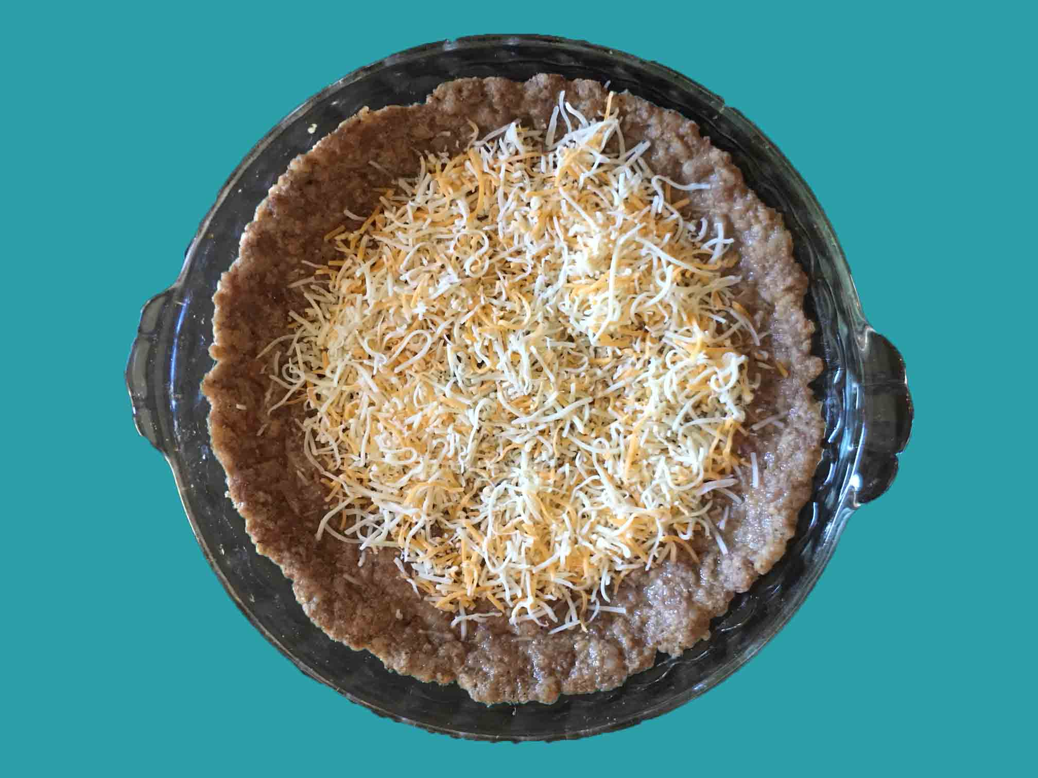 Add half of the cheese to the bottom of the pie crust evenly.