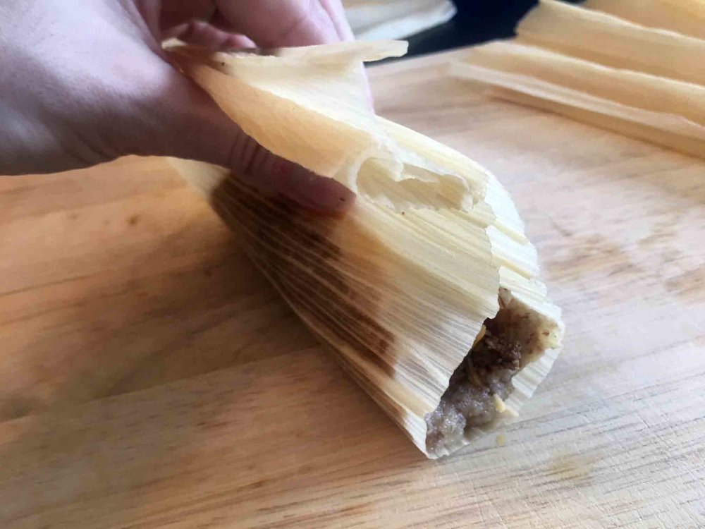 Bring the edges of the corn husk together so that the filling folds over on itself.