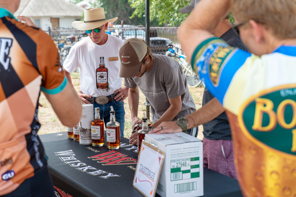Wyoming Whiskey  Distiller, Sam Meet pours samples for CGY Cyclists during the lunch stop in Kirby, WY. Photo by Nick Olson