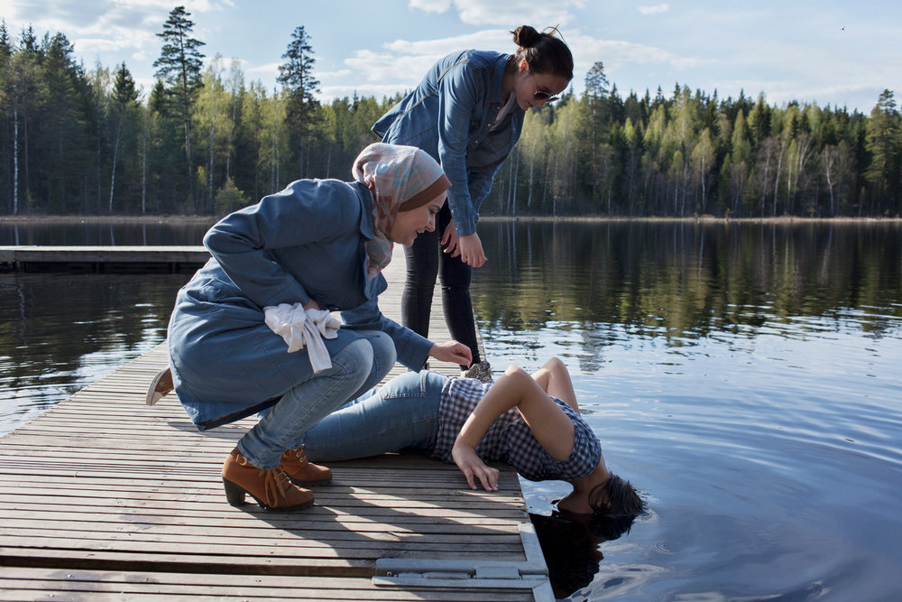 07/05/16 -- Fagersta, Sweden -- Lama, a young refugee from Syria, dip her head in the fresh water of a lake outside Fagersta with her cousin and her aunt. ©Stefano Carini | DARST