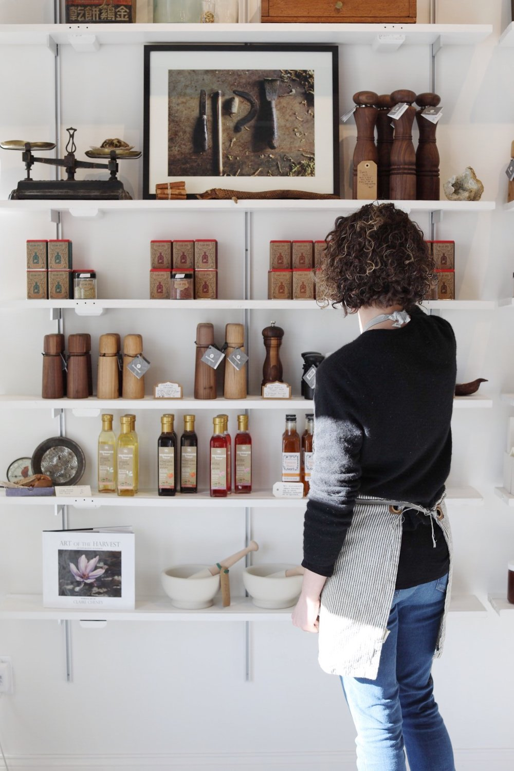 Claire Cheney stocking the shelves at Curio Spice Co.