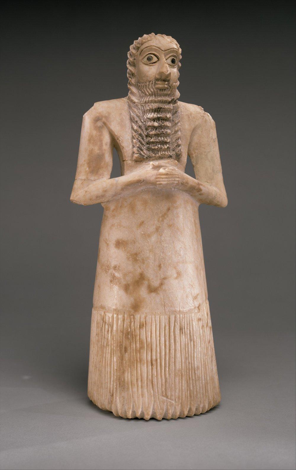 Standing Male Worshipper, photo from Metropolitan Museum of Art, Sumerian, ca. 2900–2600 B.C., Dimensions: 11 5/8 x 5 1/8 x 3 7/8 in. (29.5 x 12.9 x 10 cm), Gypsum alabaster, shell, black limestone, bitumen