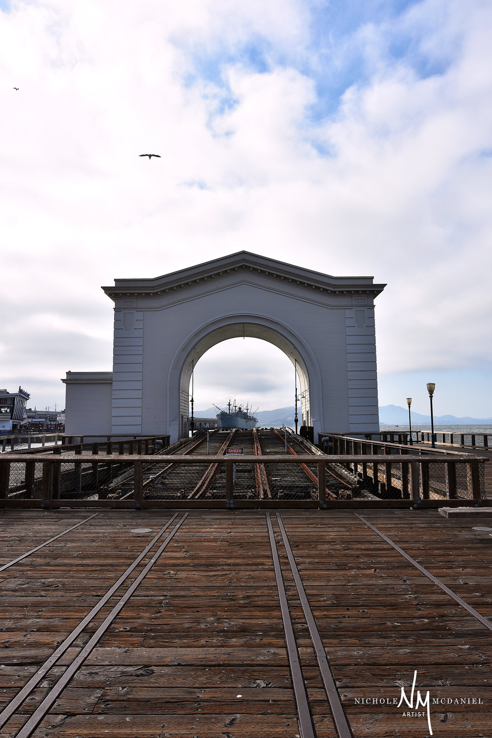 """Danger and Beauty""  What an amazing photo op. Built in 1914 and now abandoned for more then 25 years, the Arch on Pier 43 once served as a hoisting tower for loading and unloading rail cars off of ferries. It was also the location where prisoners were shipped off to Alcatraz.   Wikimapia"