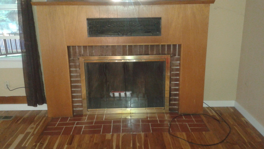 Stained brick surround covered by 1980s wood paneling, the old fireplace caught your eye, but for the wrong reasons.