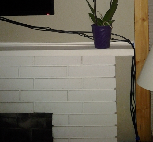 The old fireplace had a faux white-brick surround and a thin shelf serving as the mantel.