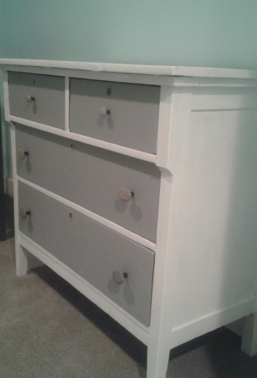 This broken and discarded dresser got a new life (and new leg to match the others). The custom knobs are made from northwest river rock.
