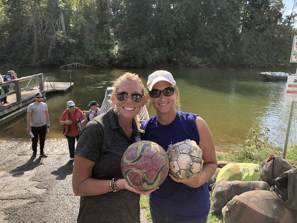 Laura Howard (left) and volunteer Lucretia Embry show off soccer ball treasures found in a KTNRB cleanup..