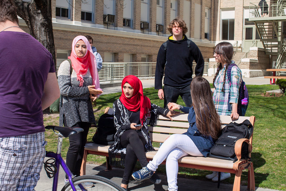 Zahraa Naser, 18, center, in red hijab, at Boise High School with her sister, standing, left, and best friend (in blue on the bench), who is, like Zahraa, from Iraq, image by Angie Smith, courtesy of the New York Times, September 2016.