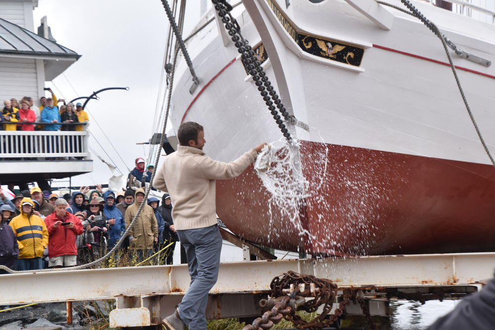 Shipwright Joe Connor smashes a bottle of champagne against the bow of 1889 bugeye  Edna Lockwood  to christen her before her return to the Miles River on Saturday, Oct. 27, 2018.