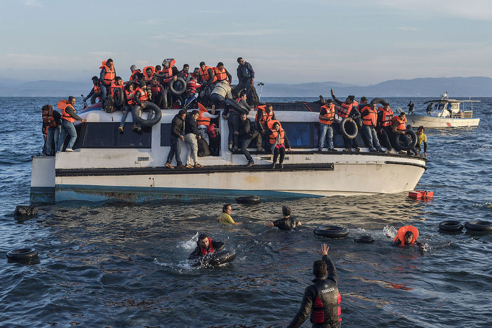 Syrian and Iraqi immigrants getting off a boat from Turkey on the Greek island of Lesbos. Image via Wikipedia Commons - User 'Ggia'