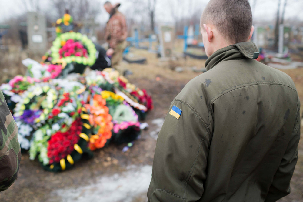 A Ukrainian soldier paying respect to the deceased. Photo courtesy of Bryce Wilson.