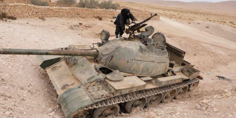An ISIS fighter stands atop a destroyed pro-Government tank.